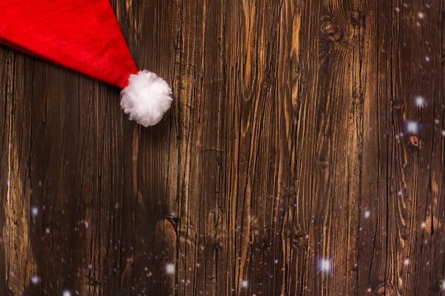 Cappello di babbo natale su sfondo in legno vecchio grunge. biglietto di auguri di natale.