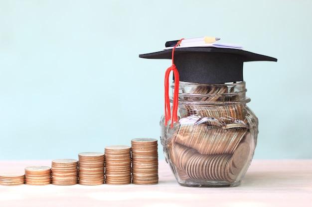 Cappello di graduazione sui soldi delle monete nella bottiglia di vetro su fondo bianco