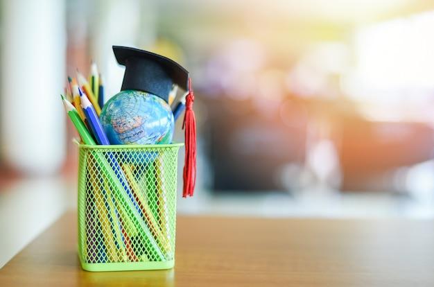 Cappello di graduazione sul concetto globale di studio di istruzione del modello del globo della terra