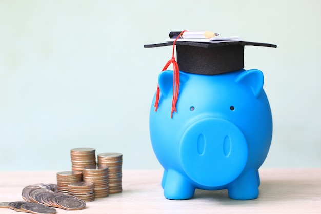 Cappello di graduazione sul porcellino e pila di soldi delle monete su bianco