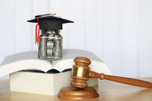 Cappello di graduazione sulla bottiglia di vetro su un libro con il martelletto di legno su fondo bianco, soldi di risparmio per il concetto di istruzione