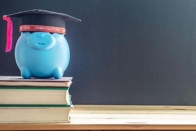 Cappello di laurea con salvadanaio su libri e sfondo lavagna