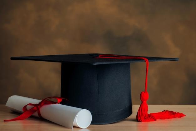 Cappello di laurea e certificato. congratulazioni per l'educazione concettuale.