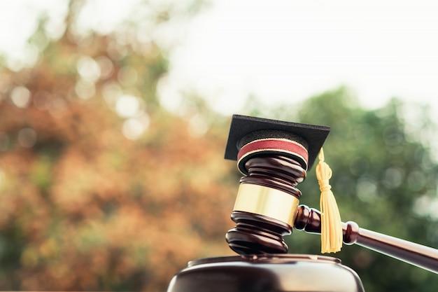 Cappello di laurea e giudice martelletto su avvocato scolastico.
