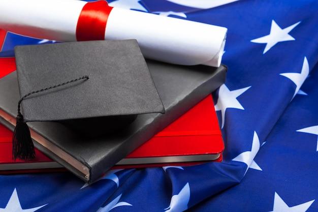 Cappello di laurea sulla bandiera degli stati uniti, concetto di educazione