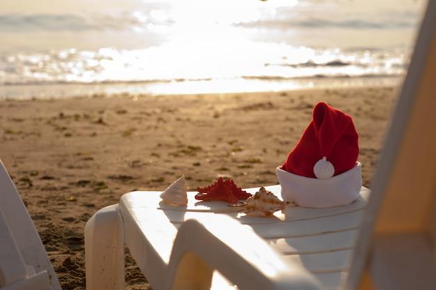 Cappello di natale su una sedia sulla spiaggia