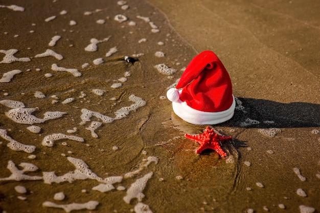 Cappello di natale sulla sabbia della spiaggia