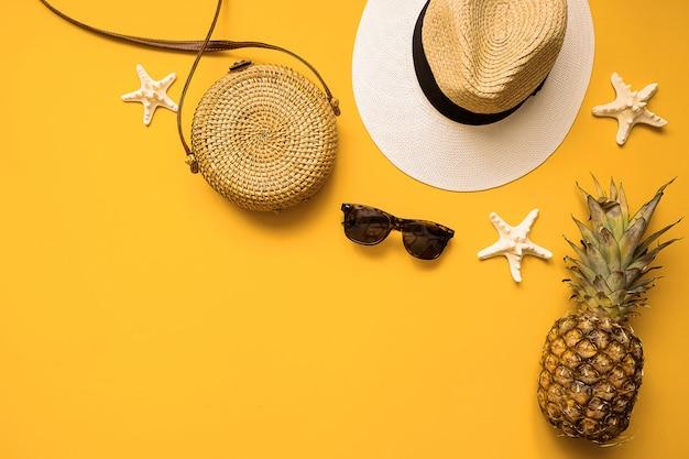 Cappello di paglia, borsa di bambù, occhiali da sole, ananas e stelle marine sopra il giallo