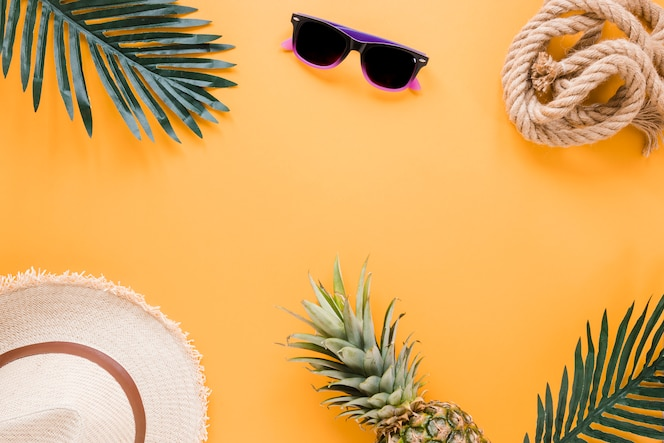 Cappello di paglia con occhiali da sole e foglie di palma