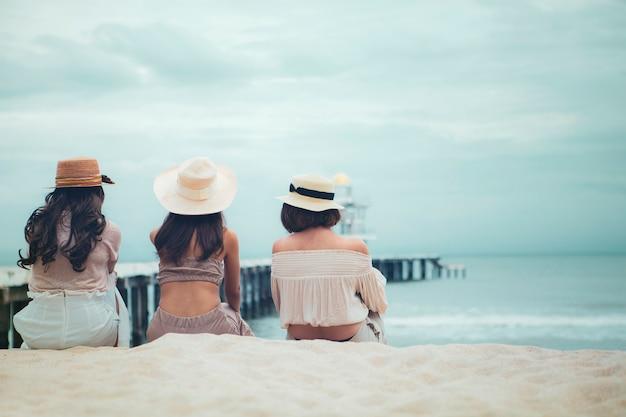 Cappello di paglia da portare delle tre donne che si siede sulla spiaggia del mare di vacanza