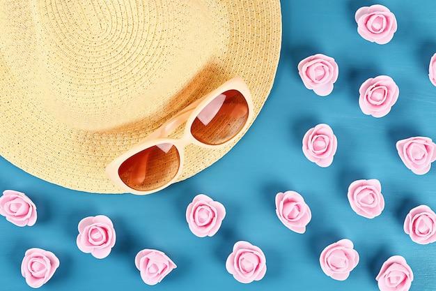 Cappello di paglia e occhiali da sole con roselline su sfondo blu. vista dall'alto. sfondo estivo distesi