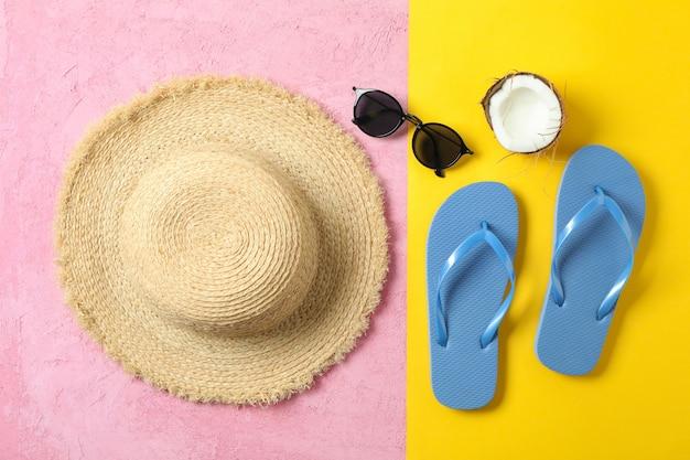 Cappello di paglia, infradito, occhiali da sole e cocco su due toni di sfondo, spazio per il testo e vista dall'alto. concetto di vacanze estive