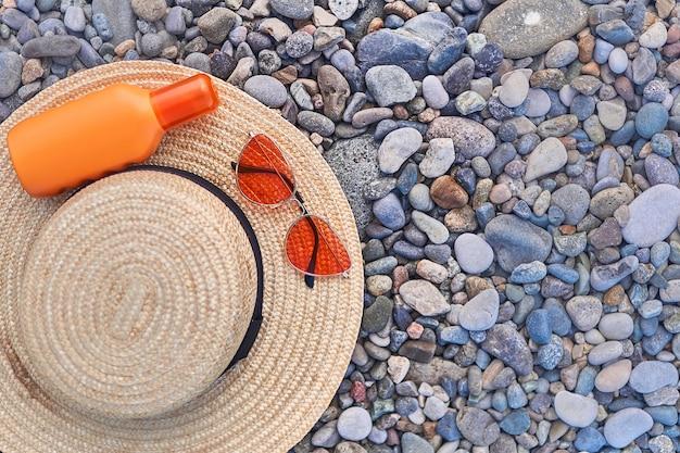 Cappello di paglia, occhiali da sole arancione brillante e una bottiglia di crema solare per la protezione solare durante il sole. copia spazio