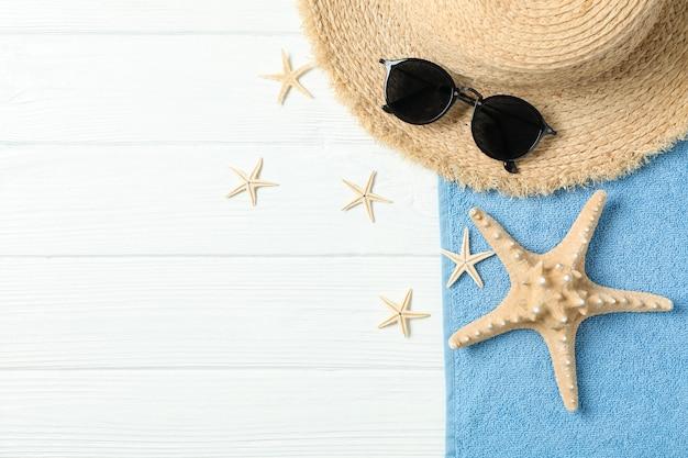 Cappello di paglia, occhiali da sole, asciugamano e stelle marine su fondo di legno bianco, spazio per testo e vista dall'alto. concetto di vacanze estive