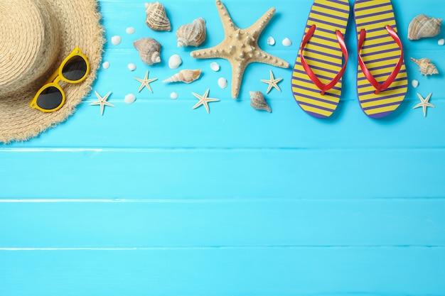 Cappello di paglia, occhiali da sole, infradito e molte stelle marine su fondo di legno di colore, spazio per testo e vista dall'alto. concetto di vacanze estive