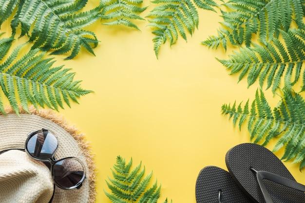 Cappello di paglia spiaggia femminile, occhiali da sole, infradito su giallo. vista dall'alto. concetto di viaggio estivo