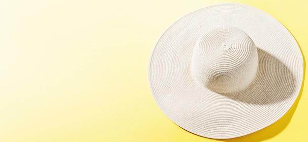 Cappello di paglia su fondo soleggiato giallo luminoso