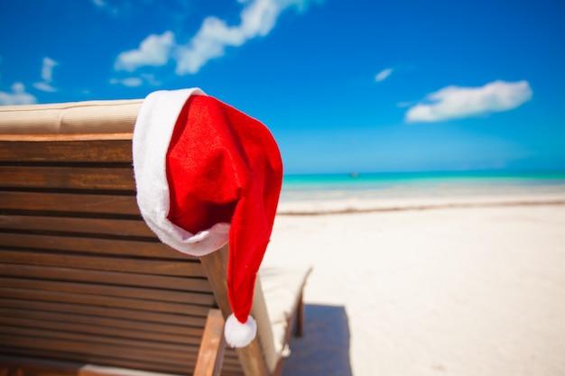 Cappello di santa sulla sedia longue alla spiaggia caraibica tropicale