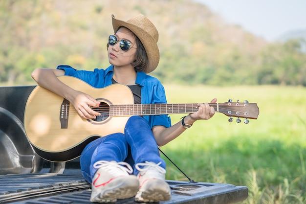 Cappello di usura della donna e suonare la chitarra sul camioncino