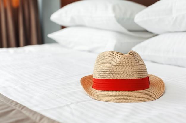 Cappello di vacanza di concetto sul letto in hotel.