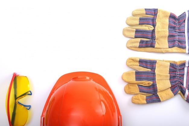 Cappello duro arancione, guanti da lavoro in pelle e occhiali di sicurezza su uno sfondo bianco. copia spazio.
