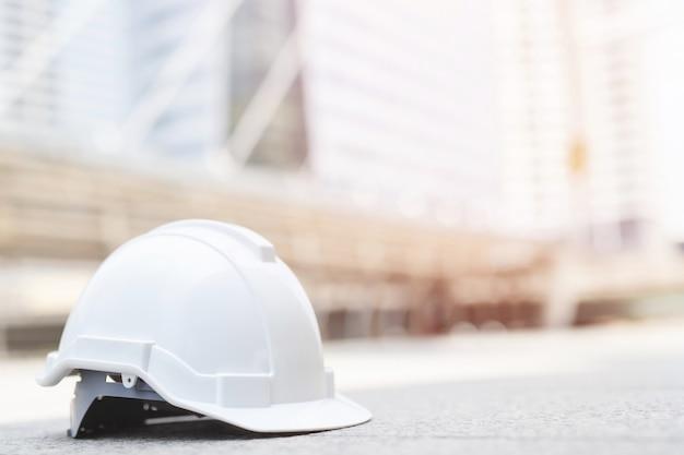 Cappello duro del casco di usura di sicurezza bianco nel progetto alla costruzione del sito sul pavimento di calcestruzzo sulla città