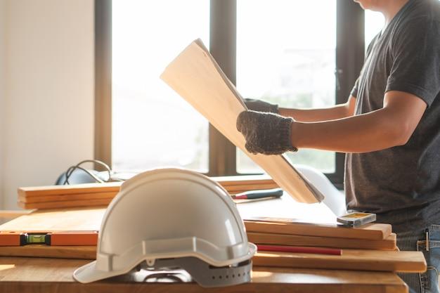 Cappello duro di sicurezza sul tavolo e lavoratore come sfondo.