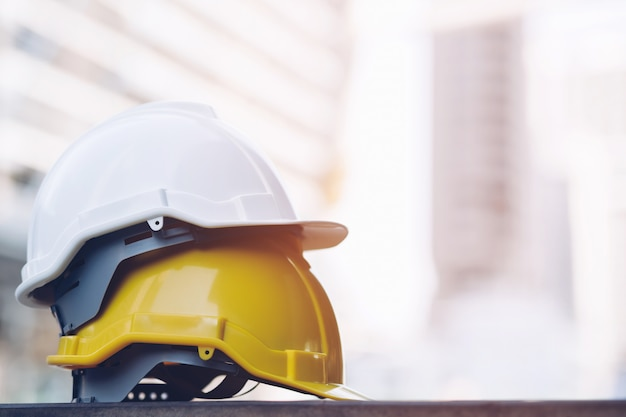 Cappello duro giallo e bianco del casco di usura di sicurezza nel progetto alla costruzione del cantiere sul pavimento di calcestruzzo sulla città