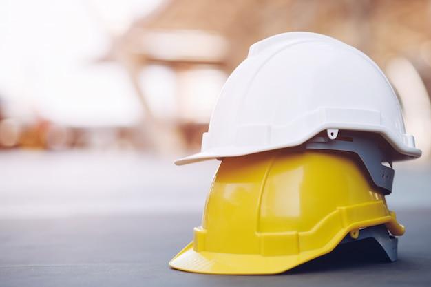 Cappello duro giallo e bianco del casco di usura di sicurezza nel progetto alla costruzione del cantiere sul pavimento di calcestruzzo