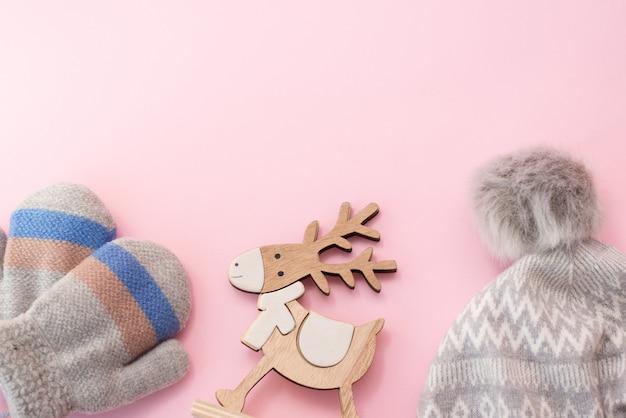 Cappello e guanti dei vestiti di inverno del bambino sul rosa