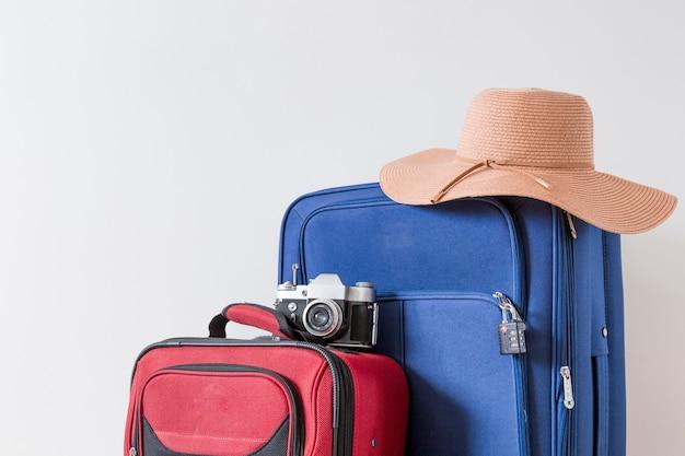 Cappello e macchina fotografica su valigie
