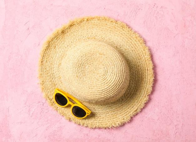 Cappello e occhiali da sole di paglia sul fondo di colore, spazio per testo e vista superiore. concetto di vacanze estive