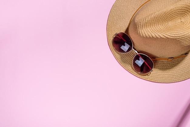 Cappello e occhiali da sole su carta rosa con stile di viaggio e di moda