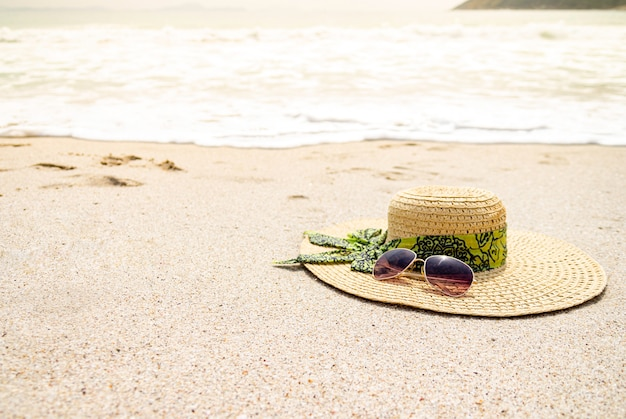 Cappello e occhiali da sole sulla spiaggia di sabbia