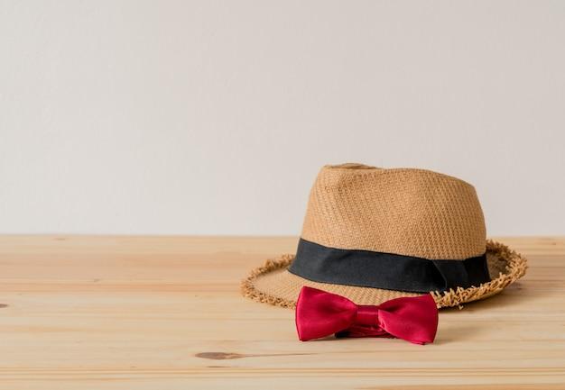 Cappello e papillon rosso sono posti sul pavimento di legno.