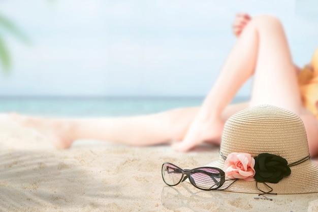 Cappello e vetri di paglia sulla spiaggia con l'immagine della sfuocatura della donna in bikini