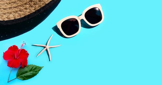 Cappello estivo con occhiali da sole, fiori di ibisco e stelle marine su sfondo blu. goditi il concetto di vacanza. copia spazio