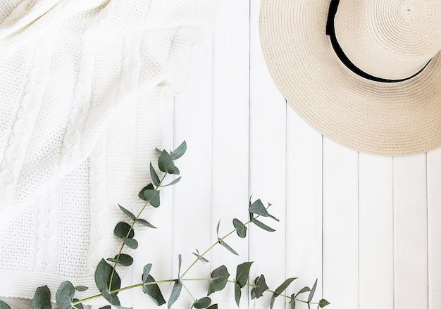 Cappello estivo e foglie di eucalipto su uno sfondo chiaro.