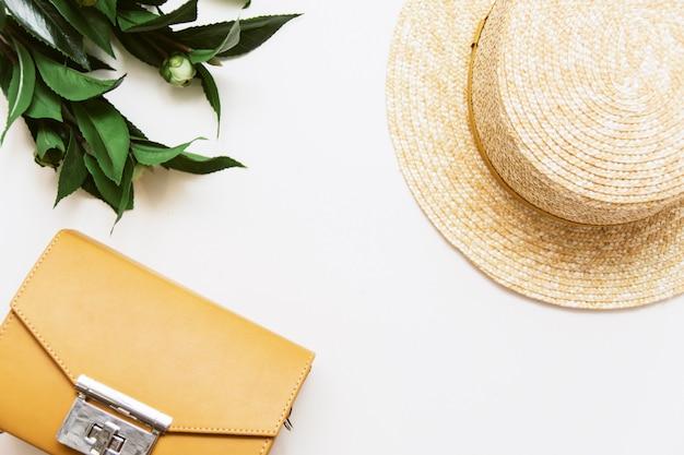 Cappello giallo della borsa, della pianta e di paglia su un fondo beige. vista dall'alto, copyspace