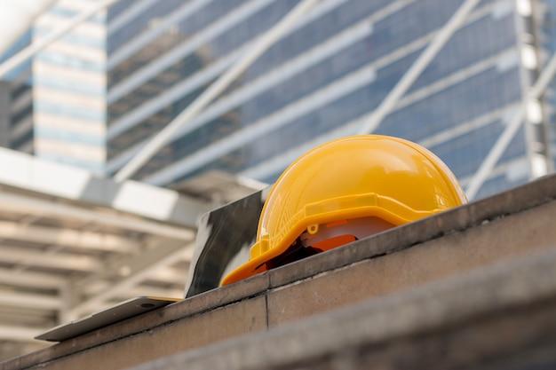 Cappello giallo di sicurezza con computer portatile sul pavimento