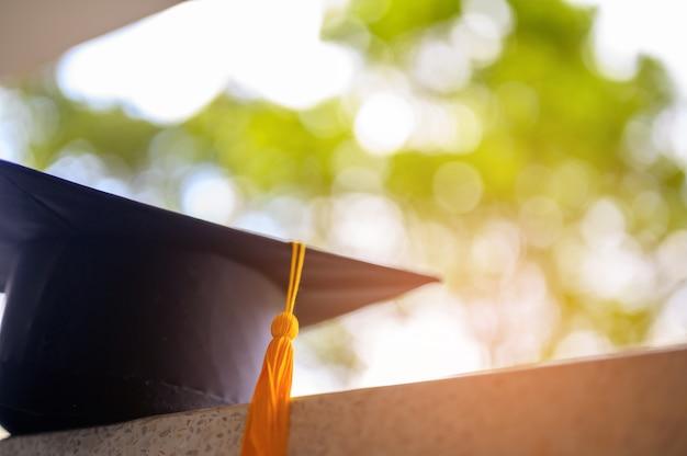 Cappello nero di graduazione del primo piano, lo sfondo è bokeh sfocato.