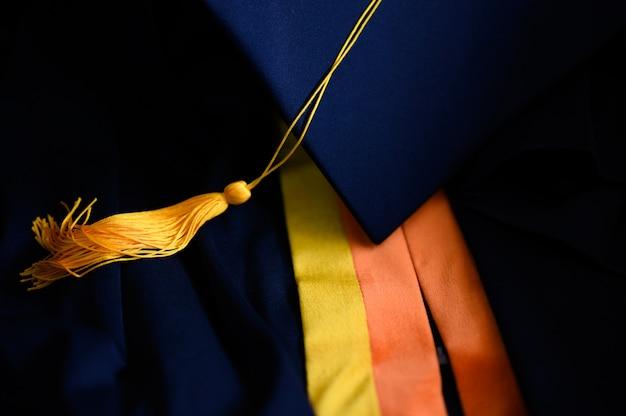 Cappello nero di graduazione di primo piano e nappa gialla posizionati sul pavimento