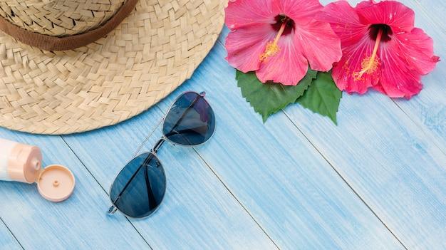 Cappello, occhiali da sole, crema solare e fiore di rosa cinese su un tavolo di legno blu.