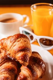 Cappello, occhiali da sole croissant con una tazza di caffè e un bicchiere di succo d'arancia su un tavolo giallo al sole