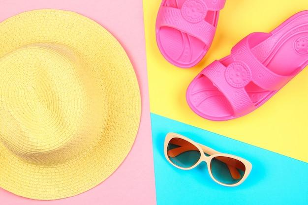 Cappello, occhiali da sole e pantofole su uno sfondo a tre colori pastello di blu, giallo e rosa.