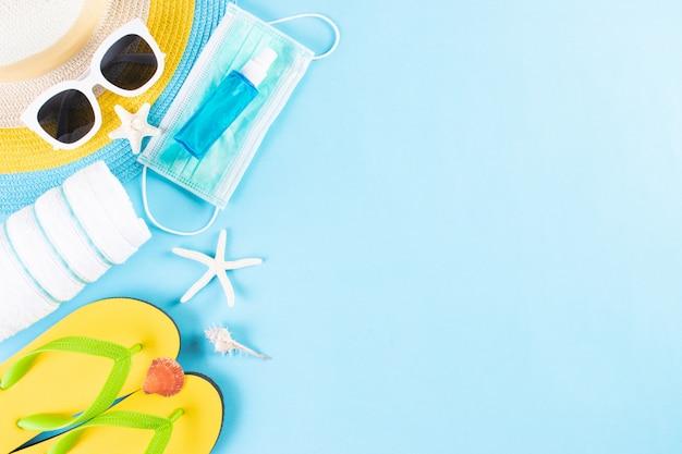 Cappello, occhiali da sole, mascherina medica, disinfettante per le mani, infradito su sfondo azzurro. estate nuova normale