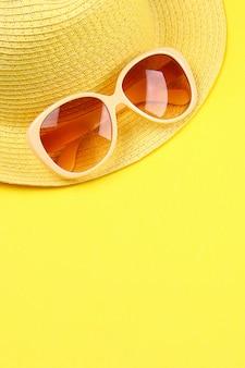 Cappello, occhiali da sole su uno sfondo giallo.