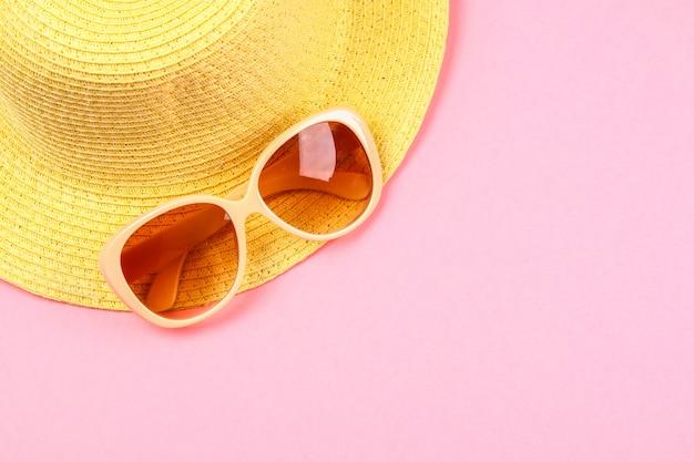 Cappello, occhiali da sole su uno sfondo rosa pastello, viola.