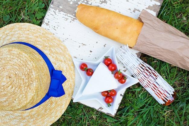 Cappello, pane, formaggio e pomodori su un piatto su erba
