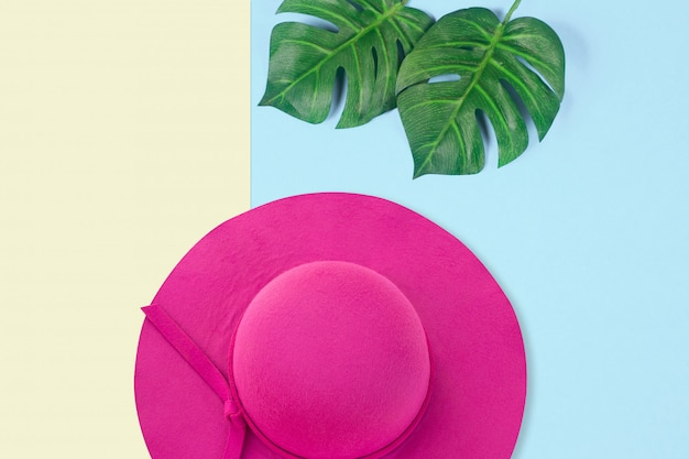 Cappello rosa della donna di estate sul fondo di colore pastello con le foglie verdi